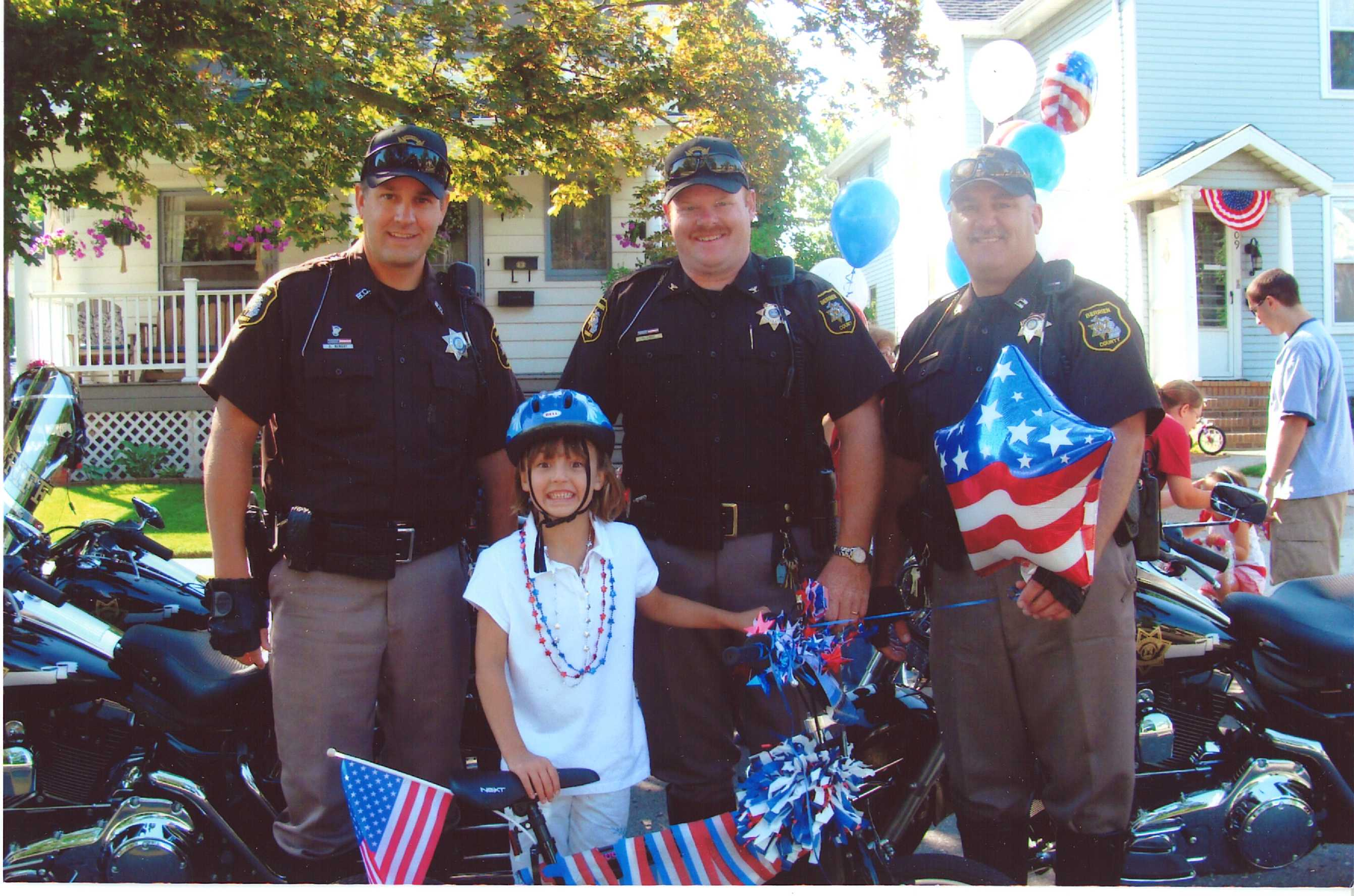 Motor Officers Pose With a Junior Cyclist